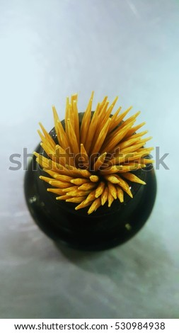 Toothpicks in a black box on white background.