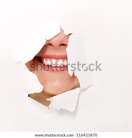 toothy smile of cheerful teen girl through hole of white paper - stock photo