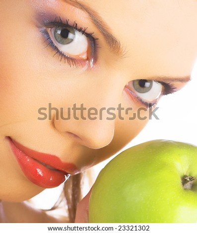 Toothy smile portrait of a beautiful young woman, holding an apple, isolated on white