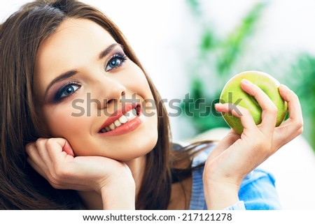 Toothy smiling young woman close up face portrait with green apple. - stock photo