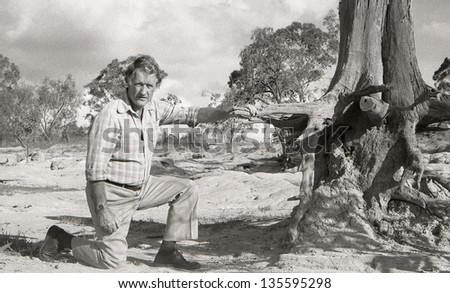 TOOWOOMBA, AUSTRALIA circa 1983: Professor Roberts shows the loss of top soil on a badly eroded farm circa 1983 near Toowoomba, Australia. Soil erosion continues to cost farmers millions of dollars. - stock photo