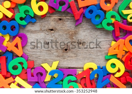 Top border of colorful toy magnetic letters and numbers over a wooden background