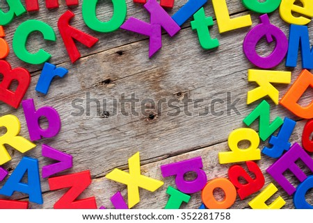 Top border of colorful toy magnetic letters over a wooden background - stock photo