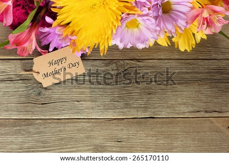 Top border of flowers with Happy Mother's Day tag against a rustic wood background - stock photo