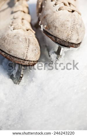 Top border of ice skates dug into the snow with space for text - stock photo