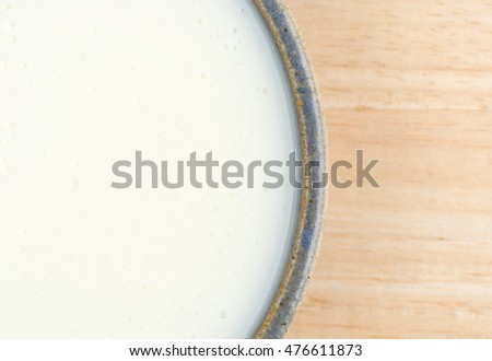 Top close view of a bowl of buttermilk on a wood table.