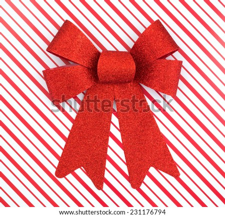 Top close view of a Christmas design red and white striped box with a large red ribbon. - stock photo