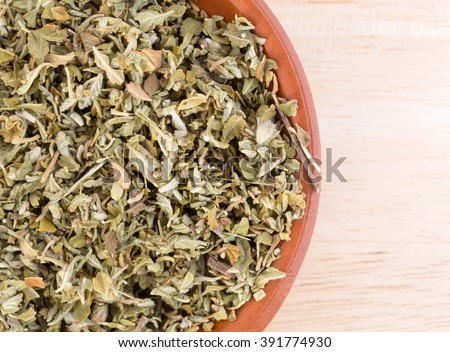 Top close view of a portion of damiana leaf in a small bowl on a wood counter top. - stock photo