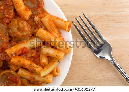 Top close view of a serving of rigatoni pasta with sausage and meatballs in a marinara sauce on a plate with a fork to the side atop a wood table.