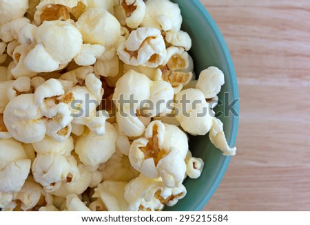 Top close view of a small bowl filled with a serving of white cheddar cheese flavored popcorn on a wood table top illuminated with natural light. - stock photo