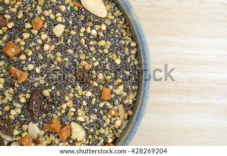 Top close view of an old stoneware bowl filled with dry breakfast cereal consisting of chia seeds, nuts, and dried fruit on a wood table top. - stock photo