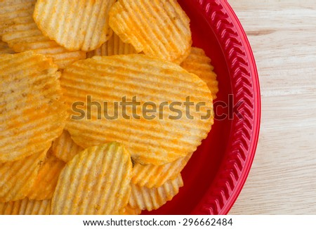 Top close view of cheddar cheese flavored potato chips on a red plastic dish atop a wood table top illuminated by natural light.