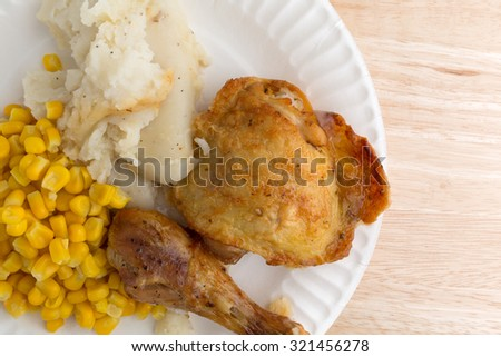 Top close view of roasted chicken, mashed potatoes and corn on a white paper plate atop a wood table top.