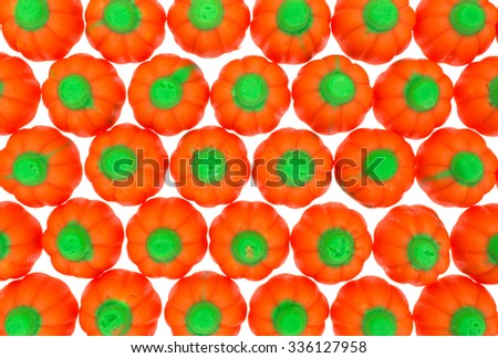 Top close view of rows of orange and green Halloween pumpkin candy on a white background. - stock photo