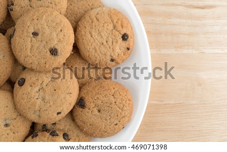 Top close view of vanilla chocolate chip cookies on a white plate atop a wood table.