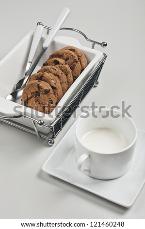 Top closeup view of biscuits in white ceramic plate with spoons and cup of milk on white wooden background - stock photo