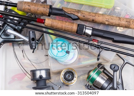 top different fishing tackles - rod, reel, line and lures in box on white background