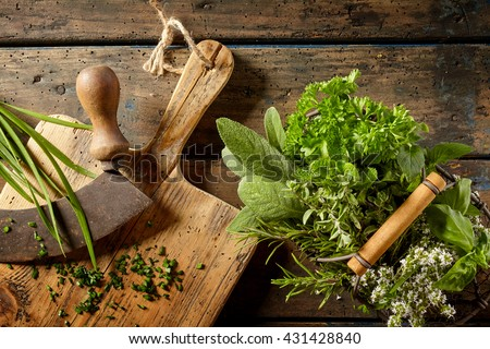 Top down first person perspective view on various herbs in basket beside cutting board on table for food preparation - stock photo