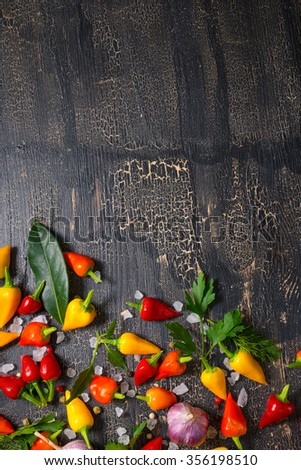 top down of yellow, red hot chili peppers, sea salt, greenery, black peppers and garlic on cracks black background - stock photo