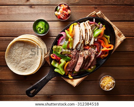top down photo of mexican steak and chicken fajitas in iron skillet with corn tortillas - stock photo