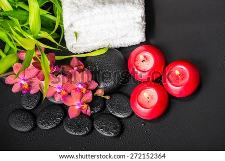 top down spa concept of blooming twig red orchid flower, phalaenopsis, bamboo with dew, towels and candles on zen basalt stones - stock photo