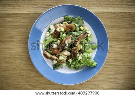 top down view of a bowl of chicken salad on wooden background - stock photo