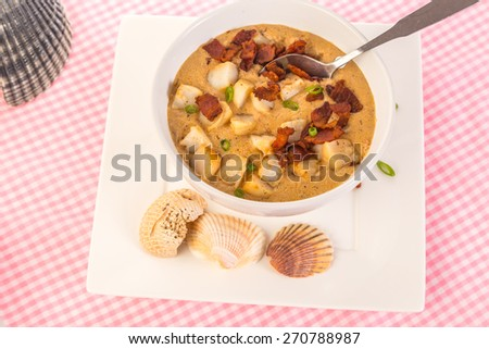 Top down view of Big chunks of sea scallops and chips of fried bacon cover this white bowl of spicy bisque on pink gingham tablecloth surrounded by seashells.