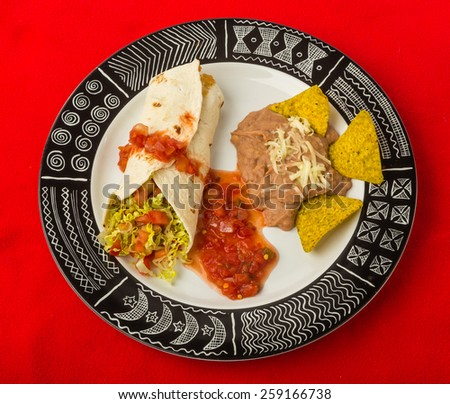 Top down view of classic Aztec Pattern Platter with Pork Burrito and refried beans on red table. - stock photo