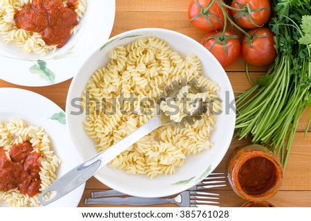 Top down view of freshly cooked rotini pasta and stainless steel spoon in bowl on table next to served plates, tomatoes, parsley and oil - stock photo