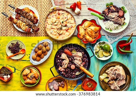 Top down view of various home made Brazilian recipes cooked and displayed on colorful textures and tablecloths - stock photo