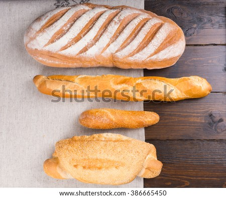 Top down view of various sized baguettes with flour coating, sesame seeds and slits on top over bakery paper and wooden table - stock photo