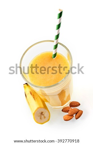 Top down view of yellow fruit and nut blended beverage with one straw next to cut banana and five almonds - stock photo