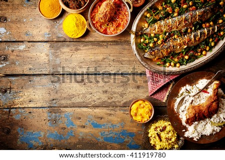 Top down view on baked fish indian style surrounded by rice, bread, sauces and various spices on weathered wooden surface with copy space - stock photo