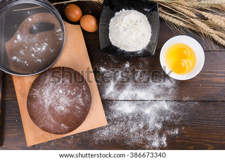 Top down view on baking ingredients of eggs, yolks, fine white flour, stalks of dried wheat rye roll and large sifter on top of cutting board - stock photo