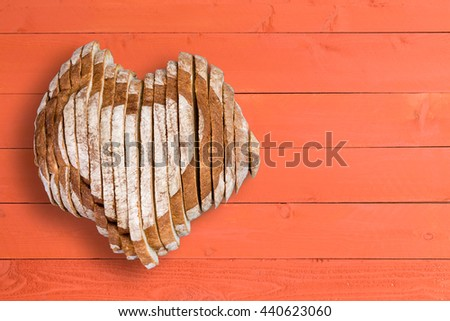 Top down view on delicious sliced bread loaf shaped as heart over wooden table surface with painted orange panels and copy space - stock photo