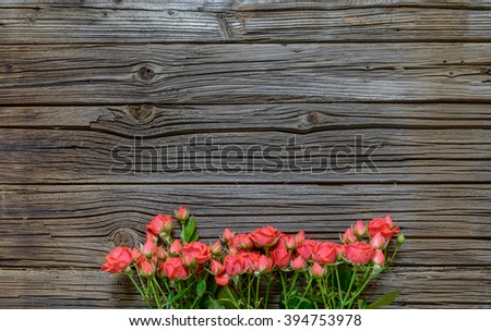 Top down view on large rose bundle in bottom half over weathered wooden table surface with copy space - stock photo