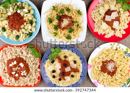 Top down view on six square and circular plates filled with different vegetables and pasta topped with herbs, sauce, cheese and other delicious ingredients - stock photo