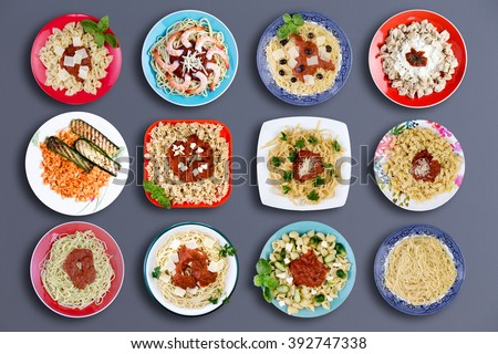 Top down view on twelve square and circular plates filled with various types of pasta topped with choice meats, fish, herbs, marinara sauce, cheese and other delicious ingredients - stock photo