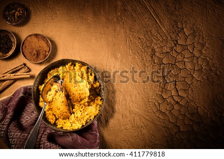 Top down view over table with Indian culinary serving of curried chicken biryani with spices and copy space - stock photo