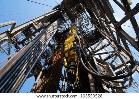 Top Drive System (TDS) and Derrick of Oil Drilling Rig - stock photo