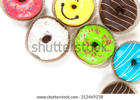 top frame from assorted glazed doughnuts in different colors on white background