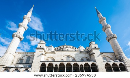Top half of Blue Mosque in Istanbul, Turkey, showing two of its six minarets - stock photo