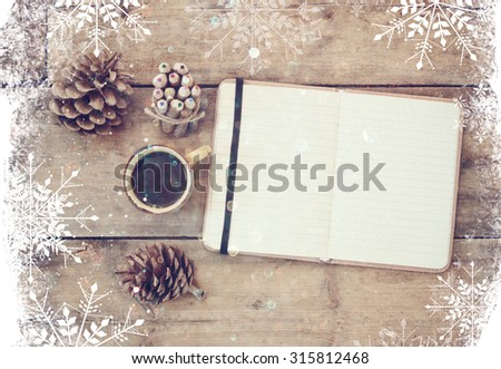 top image of open notebook with blank pages, next to pine cones and cup of coffee over wooden table. top image, glitter overly with snowflakes - stock photo