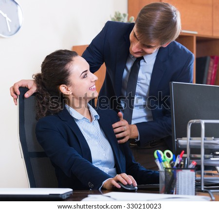 Top manager flirting with positive american adult subordinate official at workplace