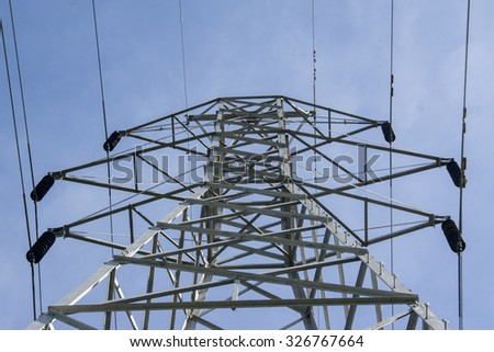 Top of a electrical tower in a middle of a field.