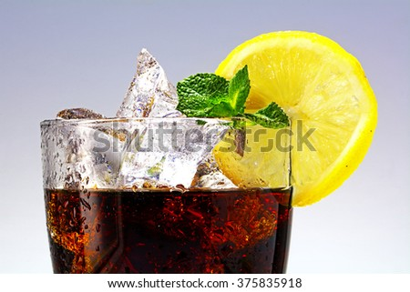 top of a glass of cola or coke with ice cubes, lemon slice and peppermint garnish, closeup with selected focus - stock photo