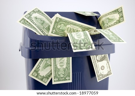 Top of a trash with one and ten dollar notes.