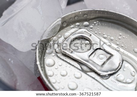 Top of aluminum cans of soda pop covered in ice and droplets of water