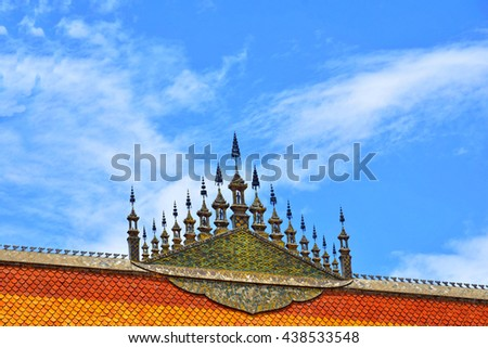 top of Buddhist Temple's roof against blue sky back ground in Luang Prabang, Laos - stock photo