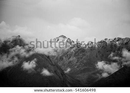 Top of High mountains, covered by snow. Atmospheric clouds linger around the peaks of the Himalaya mountain in Nepal.